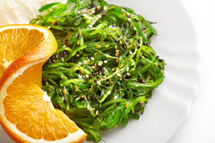 Japanese cuisine. Seaweed salad with orange in white plate Stock Image