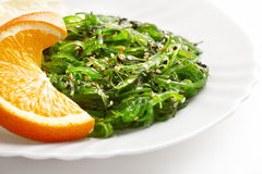 Japanese cuisine. Seaweed salad with orange in white plate Stock Photography