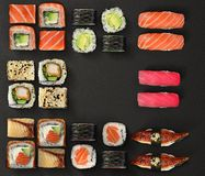 Japanese cuisine. Sushi and rolls set over dark background. Royalty Free Stock Image