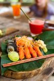 Japanese cuisine sushi and sashimi. Japanese cuisine delicious sushi rolls and fresh sashimi served on a green leaf at restaurant Stock Photos
