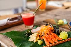 Japanese cuisine sushi and sashimi. Japanese cuisine delicious sushi rolls and fresh sashimi served on a green leaf at restaurant Stock Photography