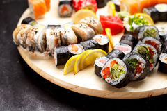 Japanese cuisine. Sushi set on a round wooden board over black concrete Royalty Free Stock Photography