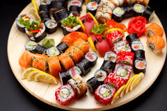 Japanese cuisine. Sushi set on a round wooden board over black concrete Royalty Free Stock Photos