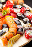 Japanese cuisine. Sushi set on a round wooden board over black concrete Royalty Free Stock Images