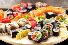 Japanese cuisine. Sushi set on a round wooden board over black concrete Stock Photos
