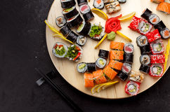 Japanese cuisine. Sushi set on a round wooden board over black concrete Stock Images