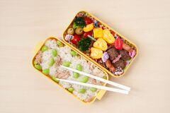 Japanese cuisine - Top view of traditional homemade Bento box with rice, meat, egg, fish, vegetables and grains