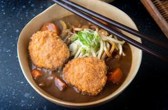 Japanese curry with udon noodle and croquettes topping. stock image