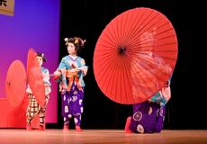 Japanese dancers with umbrellas. Kagoshima City, Japan, October 27, 2007. Japanese dancers in traditional costume perform with umbrellas onstage in the night royalty free stock images