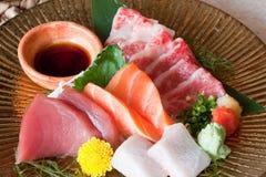 Japanese dishes - sashimi. A set of nice presentation sashimi dish - tuna, salmon, yellow tail, japanese beef sashimi with japanese soya sauce and wasabi close Royalty Free Stock Photography