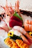 Japanese dishes - sashimi. A set of nice presentation sashimi dish - salmon, yellow tail, giant sweet shrimp, sea urchin and tuna preserved on ice Royalty Free Stock Image