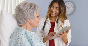 Japanese doctor showing elderly patient information on tablet computer Stock Photography