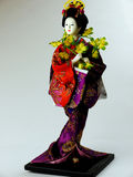 Japanese doll. Dressed in kimono and flowers around her neck Royalty Free Stock Images