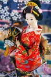 Japanese Doll. On blue flower background royalty free stock image