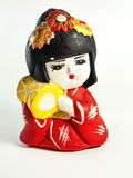 Japanese doll ceramic pottery. Child holding a toy drum of ceramic sculpture and drawings by craftsman royalty free stock photo