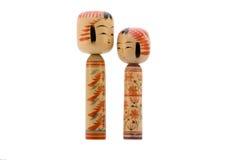 Japanese dolls on white background. Japanese Kokeshi dolls photograph facing each other on white background stock image