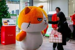 Japanese dresses up a cute cartoon mascot. TOKYO, JAPAN - NOVEMBER 28 2015: Unidentified Japanese dresses up a cute cartoon mascot cat in front of Bic Camera stock photos