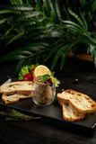 Japanese duck pate with warm ciabatta on a black plate on a black wooden background stock photos