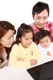 Japanese family of four on laptop computer Royalty Free Stock Image