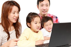 Japanese family of four on laptop computer Royalty Free Stock Photos