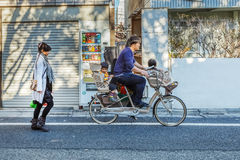 Japanese Family in Tokyo. TOKYO, JAPAN - NOVEMBER 23: Japanese Family in Tokyo, Japan on November 23, 2013. Unidentified japanese father carries his children on Stock Photos