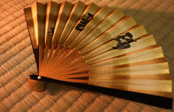 Japanese fan. An opened Japanese gold fan with calligraphy about mediation of good wishes on the mat Stock Photography