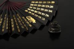 Japanese fan with black massage stones. Black massage stones and a japanesse fan on a black background Stock Photos