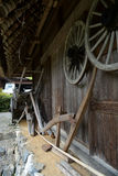 Japanese Farm Tools Outside Mountain House. Historic Japanese farm tools outside of a mountain house with a thatched roof. Located in the Kyoto prefecture of Royalty Free Stock Photo