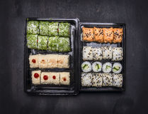 Japanese fast food, sushi set with two variousingredients in plastic containers on dark rustic background, top view Stock Image