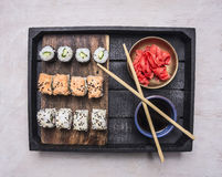 Japanese fast food, sushi set in a wooden tray with soy sauce and ginger , Asian cuisine wooden rustic background top view clos Stock Images