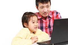 Japanese father and daughter on laptop computer Stock Image