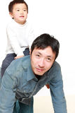 Japanese father and his son play horse-ride Royalty Free Stock Image