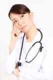 Japanese female doctor thinks about something Royalty Free Stock Image