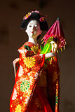 Japanese female kimono doll wearing red paper umbrella with flowers in hair and green glowing tritium trinket Royalty Free Stock Photo