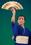 Japanese Festival Dancer. Kagoshima City, Japan, October 27, 2007. An older Japanese dancer in kimono perform with a fan onstage in the night portion of the stock images