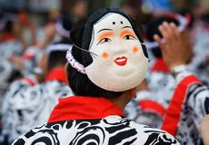 Japanese Festival Dancer with a mask. A Japanese man dances in a festival while wearing a happi coat and having a mask of a smiling woman on the back of his head stock images