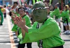 Japanese Festival Dancers. Kagoshima City, Japan, October 28, 2007. A man wearing a buddha mask green hakama jacket leading a group dancing during the Taniyama stock photo