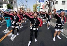Japanese Festival Dancers. Kagoshima City, Japan, October 28, 2007. Men and women in black happi coats dancing in symmetry during the Taniyama Furusato Matsuri royalty free stock photos