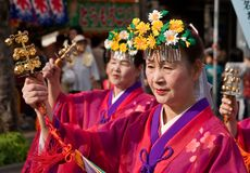 Japanese Festival procession. Kagoshima City, Japan, October 28, 2007. Women in red yukata kimono and wearing flowers in their hair lead a procession during the stock image