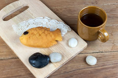 Japanese fish shaped pancake. Taiyaki, japanese fish shaped pancake. Eaten with hot tea on wood table Stock Photo