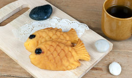 Japanese fish shaped pancake. Taiyaki, japanese fish shaped pancake. Eaten with hot tea on wood table Stock Photography
