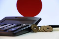 Japanese five Yen three coins JPY on white floor with black calculator and pencil on Japan flag background. stock photo