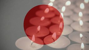 Japanese Flag with candles. Digital composite of moving Japanese flag against burning candles going out in the background stock video