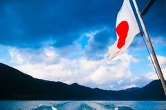 Japanese flag on flag pole against a blue sky Stock Photo