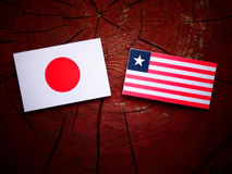 Japanese flag with Liberian flag on a tree stump isolated. Japanese flag with Liberian flag on a tree stump Stock Images