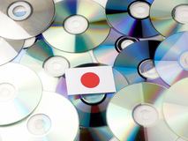 Japanese flag on top of CD and DVD pile isolated on white. Japanese flag on top of CD and DVD pile isolated Royalty Free Stock Image
