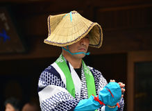 Japanese folk dancer wearing straw hat. Koya, Japan - June 14, 2011: Folk dancer in traditional clothes during Aoba festival, an annual event celebrating the stock image