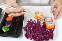 Japanese food. Closeup image of hand and chopstick prepare sushi japanese food Royalty Free Stock Photos