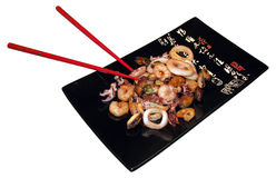 Japanese food. Black square plate with red sticks and sea food royalty free stock images