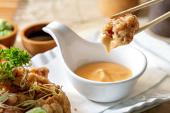Japanese food grilled chicken karage served with mayo sauce. Close up portrait of grilled chicken karage served with mayo sauce using chopsticks Royalty Free Stock Images